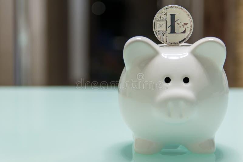 Керамическая копилка с серебряной стойкой litecoin на верхней части стоковые фото