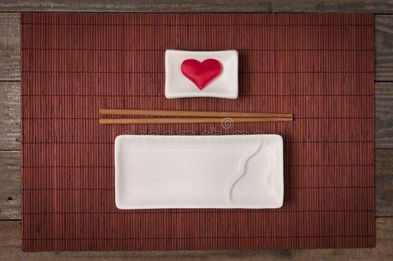 Керамическая плита для суш и японской кухни с палочкой и шаром для соевого соуса с сердцем внутри взгляда сверху стоковая фотография