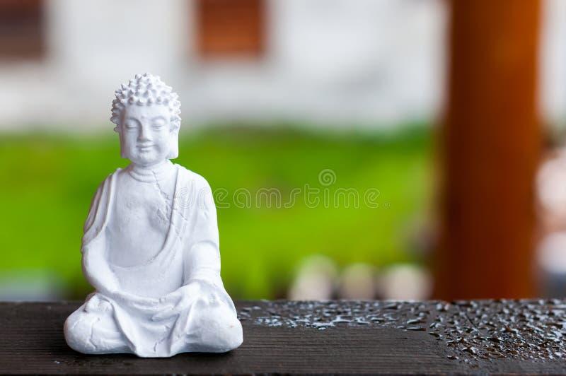 Керамическая статуя Будды Дзэн размышляя с запачканной предпосылкой текстуры Концепция йоги стоковое изображение
