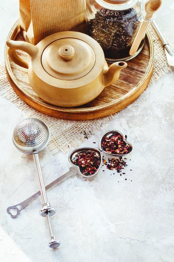 Керамические бак чая, infuser чая металла и чашка черного чая Состав с аксессуарами чая на белой предпосылке стоковое фото