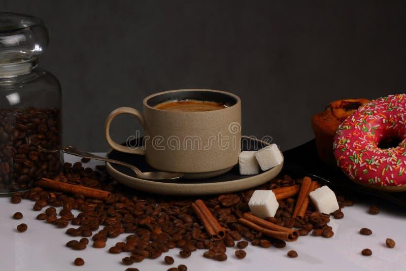 Керамические кофейная чашка и донут с сахаром на серой предпосылке стоковые изображения