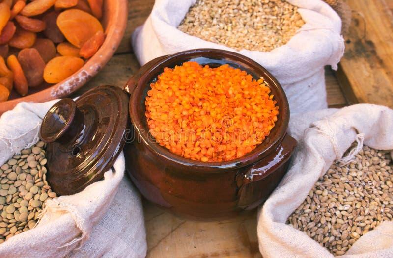Керамический глиняный горшок с красными чечевицами и мешками бобов и зерна в продовольственном рынке стоят стоковое фото rf