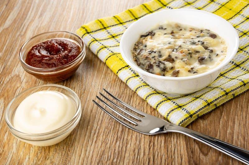 Кетчуп и майонез, julienne с цыпленком, грибом в шаре на салфетке, вилке на  стоковые изображения rf