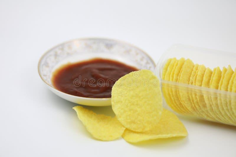 Кетчуп томата на плите и картофельных стружках в коробке Диета, жиреть стоковое фото