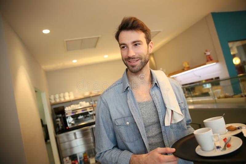 Кельнер в кофейне служа его гости стоковое изображение