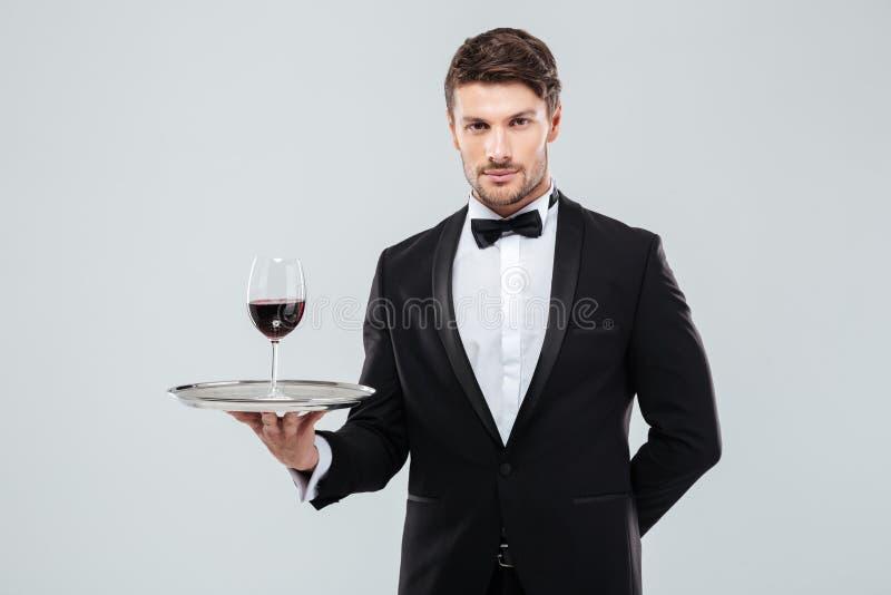 Кельнер в смокинге держа стекло красного вина на подносе стоковая фотография rf