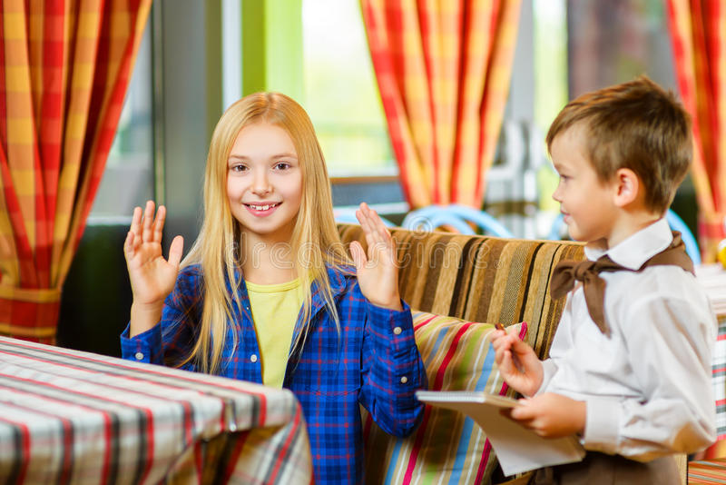 Кельнер мальчика признавает заказ в кафе или стоковая фотография