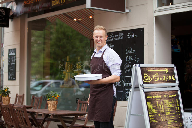 Кельнер с подносом в кофейне стоковые фотографии rf