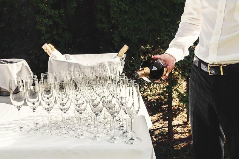 Кельнер льет стильные роскошные стекла для шампанского на таблице для стоковая фотография