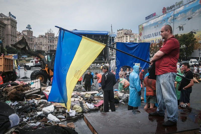 КИЕВ, УКРАИНА - 9-ОЕ АВГУСТА 2014: Человек отказываясь украинский флаг на квадрате Maidan баррикад во время их удаления стоковая фотография rf