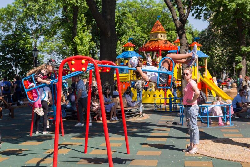 Киев, Украина - 19-ое мая 2019: Дети в присутствии к их родителям едут на качании на спортивной площадке стоковая фотография rf