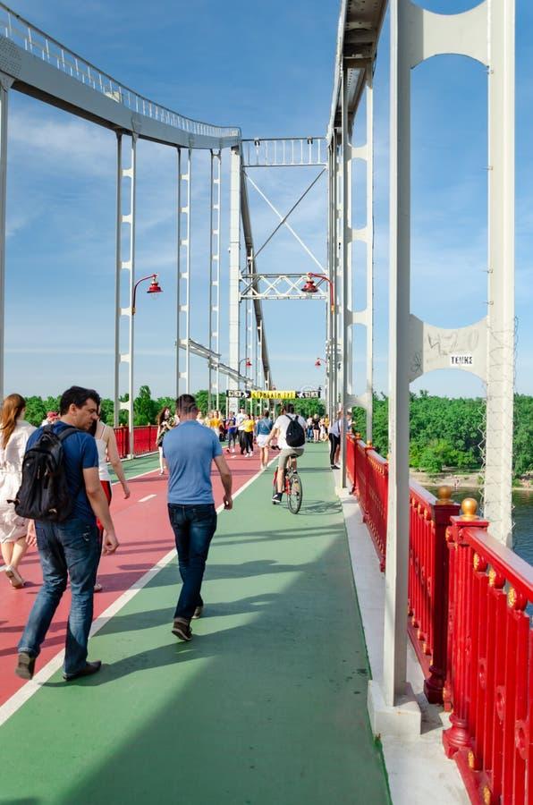 Киев, Украина - 18-ое мая 2019 Мост парка над рекой Dnipro Люди идя вдоль пешеходного моста на выходных стоковая фотография