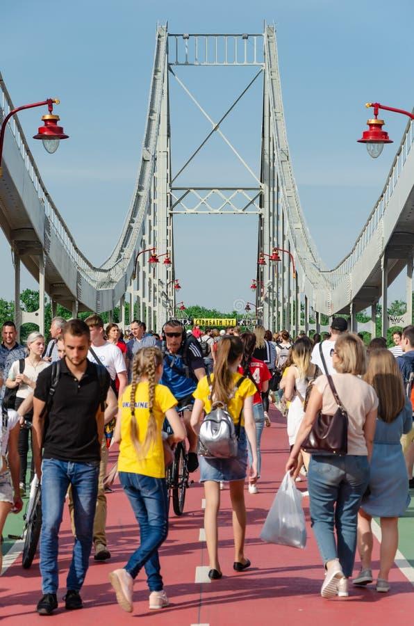 Киев, Украина - 18-ое мая 2019 Мост парка над рекой Dnipro Люди идя вдоль пешеходного моста на выходных стоковое фото