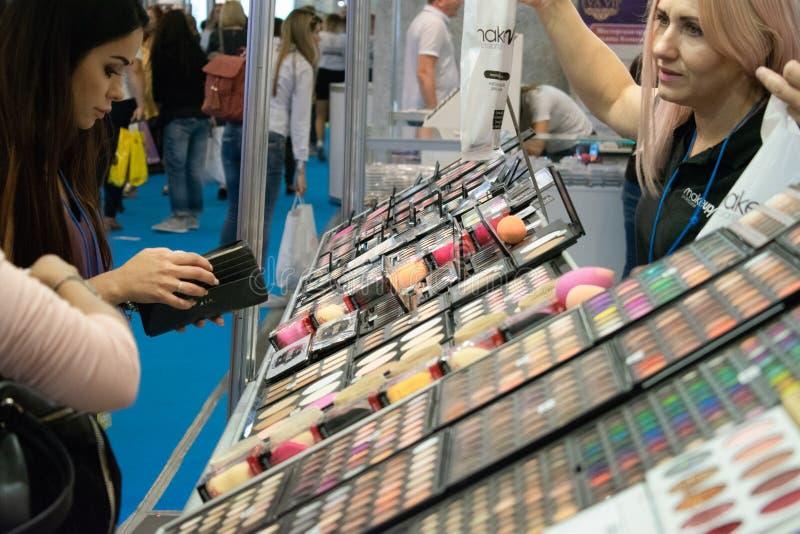 Киев, Украина 19-ое сентября 2018: Молодая женщина выбирает декоративные косметики на стойке магазина красоты во время шоу красот стоковые фотографии rf