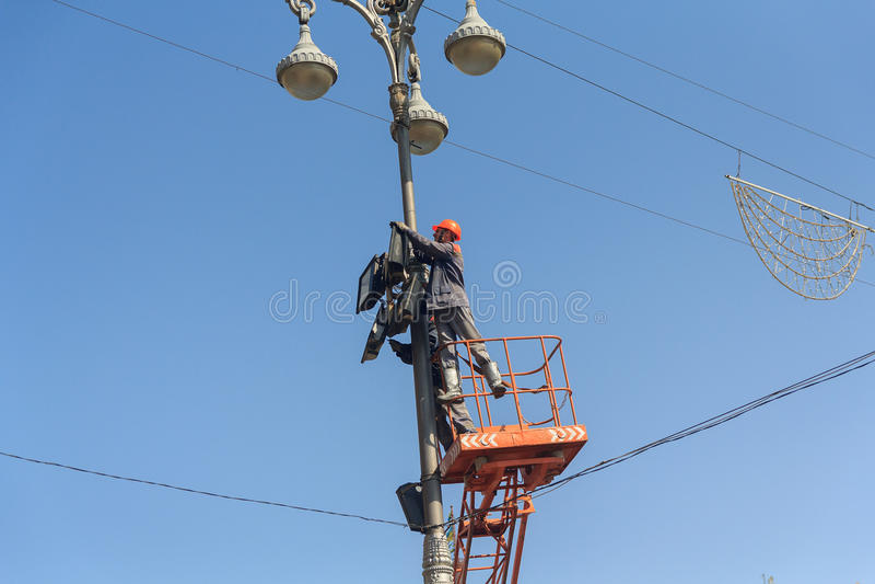 Киев, Украина - 18-ое сентября 2015: Электрики ремонтируя оборудование освещения стоковые фото