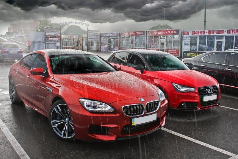 Киев, Украин 20-ое мая 2014, 2 красных автомобиля в дожде BMW M6 и Audi A3 стоковое изображение rf