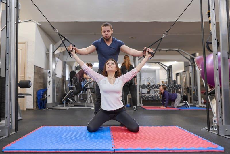 Киев UA, 28-03-2019 Зрелая женщина делая тренировку на имитаторах понижения давления с реабилитацией тренера Физиотерапевт спорт стоковые изображения rf