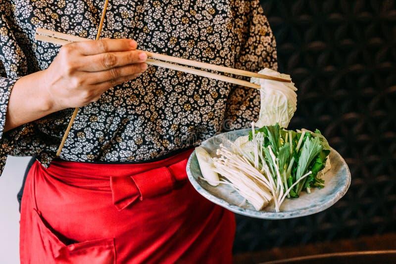 Кимоно женщины нося держа капусту над овощами Sukiyaki установило включая капусту, ложное Пак choi, морковь, шиитаке стоковые фотографии rf