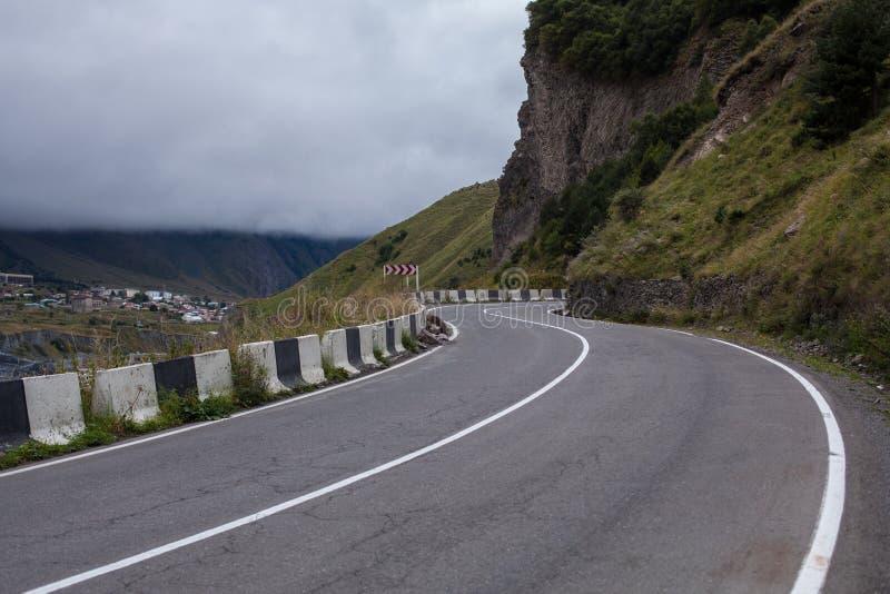 Кинематографический ландшафт дороги Throuth дороги асфальта горы С пасмурным небом стоковое фото