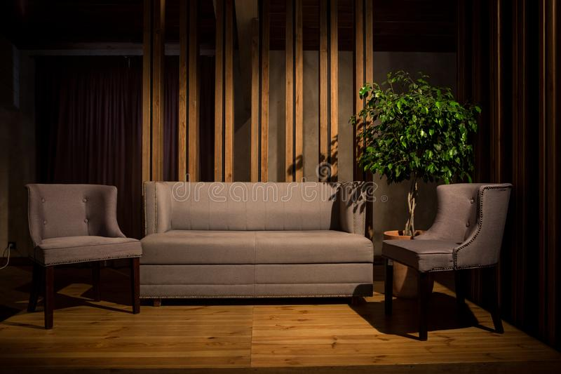 Кинематографический свет Серая софа и 2 серых стуль на деревянных ногах стоят на коричневом деревянном подиуме стоковая фотография rf