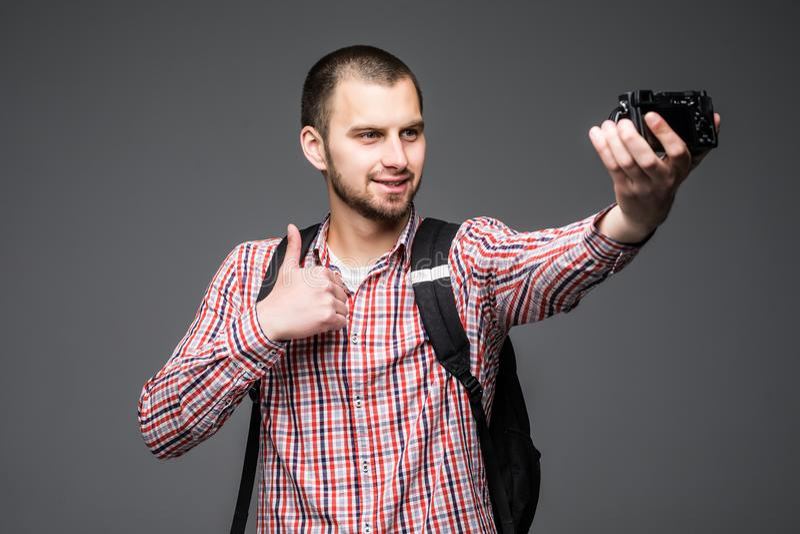 Киносъемка себя блоггера молодого человека для его видео- блога изолированного на серой предпосылке Vlog стоковое изображение