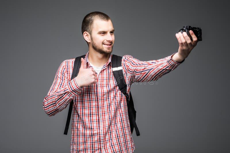 Киносъемка себя блоггера молодого человека для его видео- блога изолированного на серой предпосылке Vlog стоковые изображения