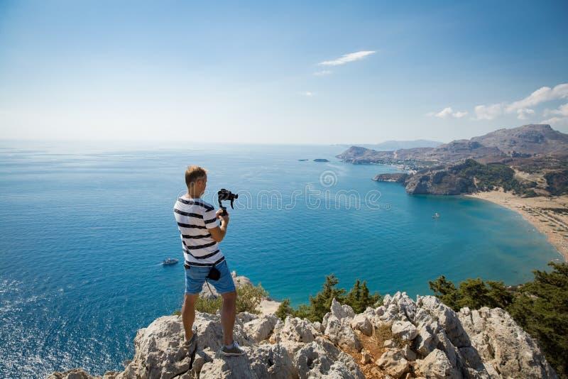 Киносъемка человека на камере на верхней части горы стоковое изображение rf