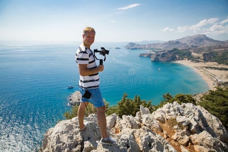 Киносъемка человека на камере на верхней части горы стоковые фото