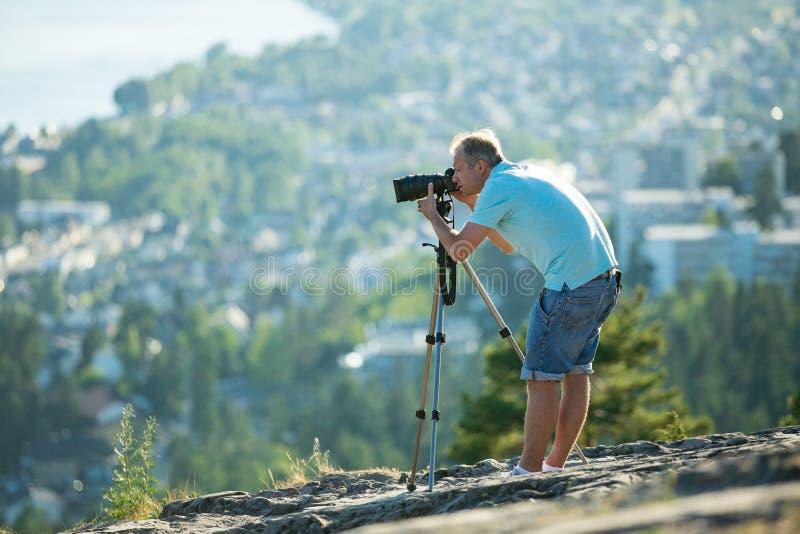 Киносъемка человека на камере с треногой на верхней части горы стоковая фотография rf