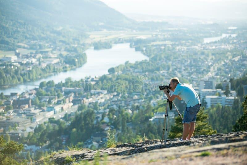 Киносъемка человека на камере с треногой на верхней части горы стоковая фотография