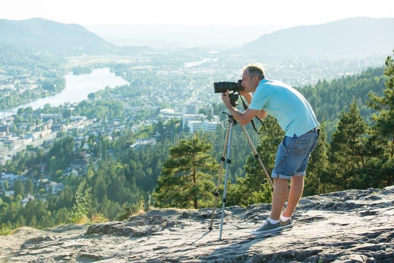 Киносъемка человека на камере с треногой на верхней части горы стоковое фото rf