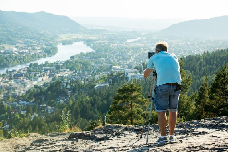 Киносъемка человека на камере с треногой на верхней части горы стоковые изображения rf