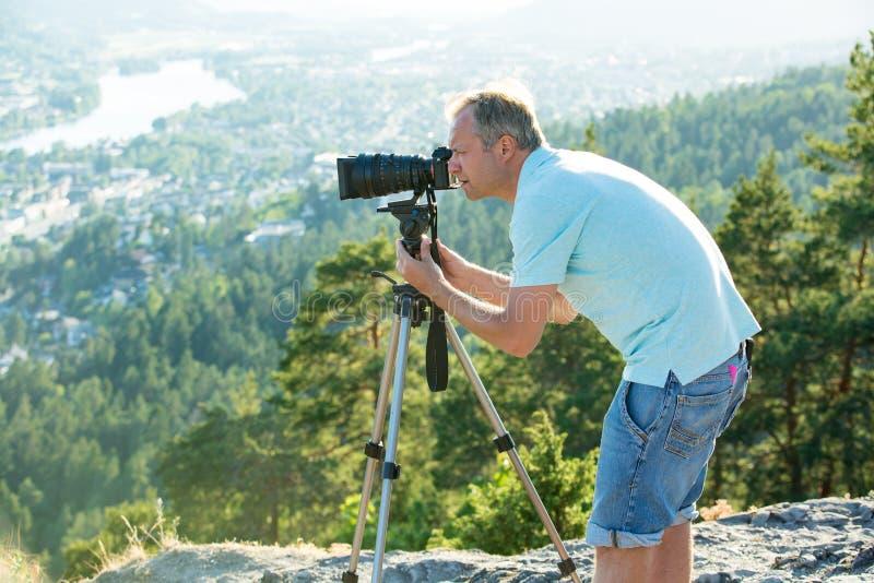 Киносъемка человека на камере с треногой на верхней части горы стоковые изображения