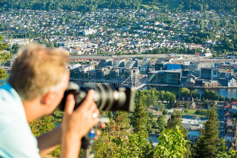 Киносъемка человека на камере с треногой на верхней части горы стоковое фото