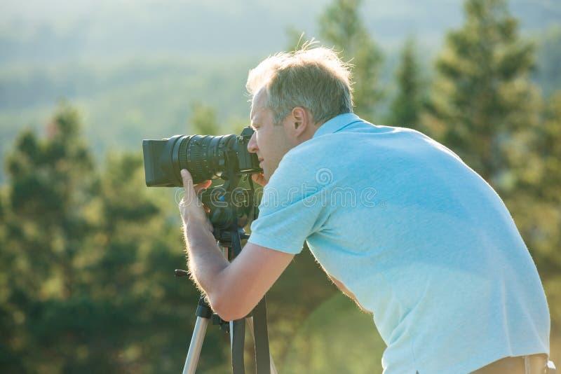 Киносъемка человека на камере с треногой на верхней части горы стоковое изображение