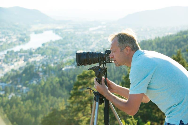 Киносъемка человека на камере с треногой на верхней части горы стоковые фото