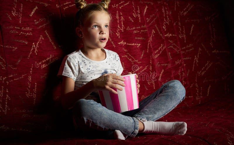 Кино детей: Одна девушка школьницы смотрит фильм дома на большой красной софе и ест popkort от красного ведра стоковые изображения rf