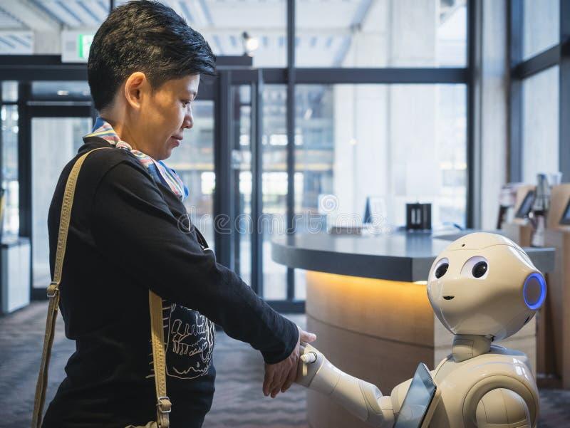 КИОТО, ЯПОНИЯ - 14-ОЕ АПРЕЛЯ 2017: Рука встряхивания приветствию робота перца с азиатским туристским туризмом Японией стоковые фото