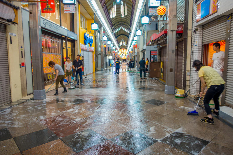 КИОТО, ЯПОНИЯ - 5-ОЕ ИЮЛЯ 2017: Неопознанные люди очищая с вениками экстерьер o их рынки магазинов и стоковые фотографии rf