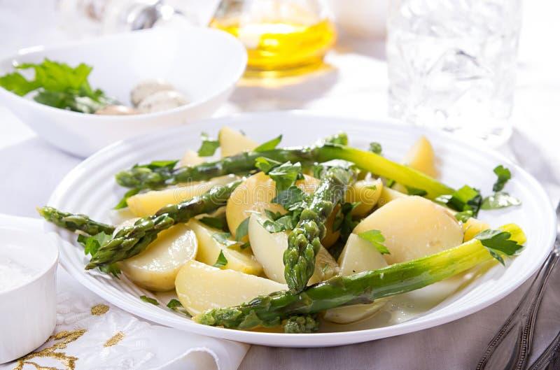 Кипеть картошка с зажаренной зеленой спаржей на белой плите над o стоковая фотография rf