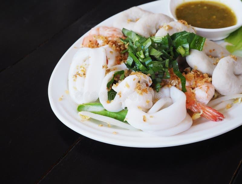 Кипеть погружение морепродуктов с горячим и кислым соусом на белой плите стоковые изображения