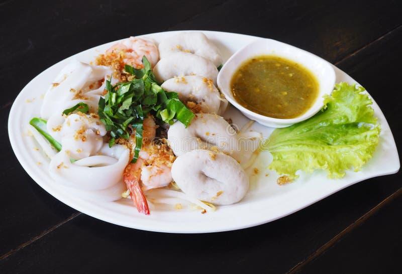 Кипеть погружение морепродуктов с горячим и кислым соусом на белой плите стоковые фото