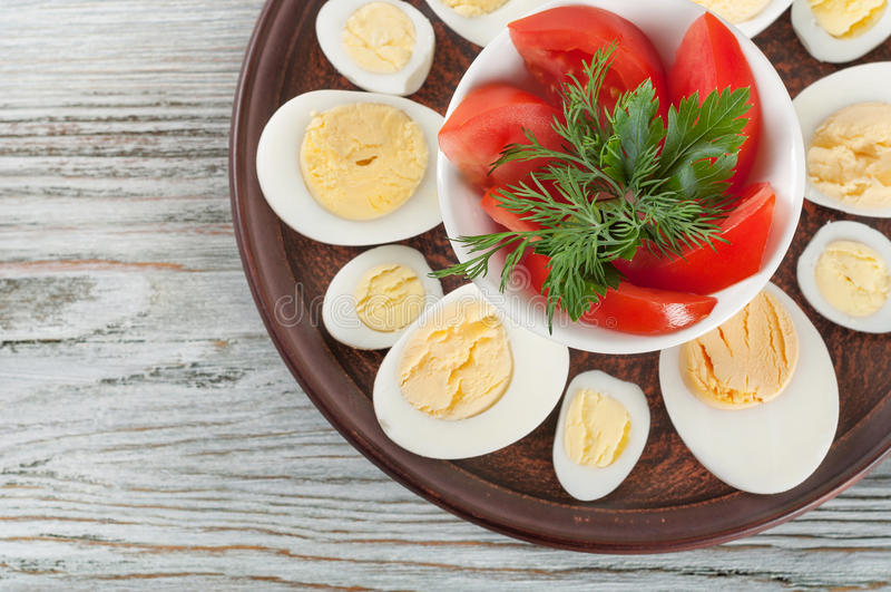 Кипеть яичка курицы и красный томат стоковая фотография