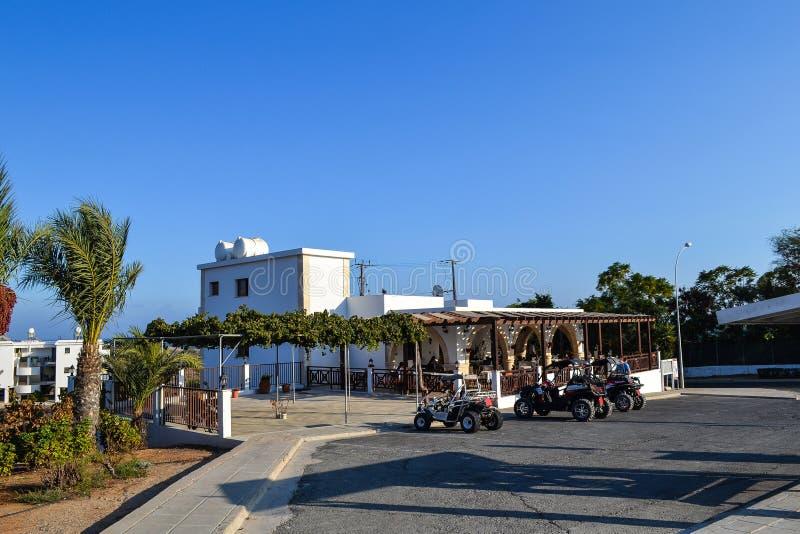 КИПР, Ayia Napa, - 20-ое сентября 2015: Кафе улицы Люди имеют завтрак на улице припаркованы велосипеду квада стоковое изображение rf