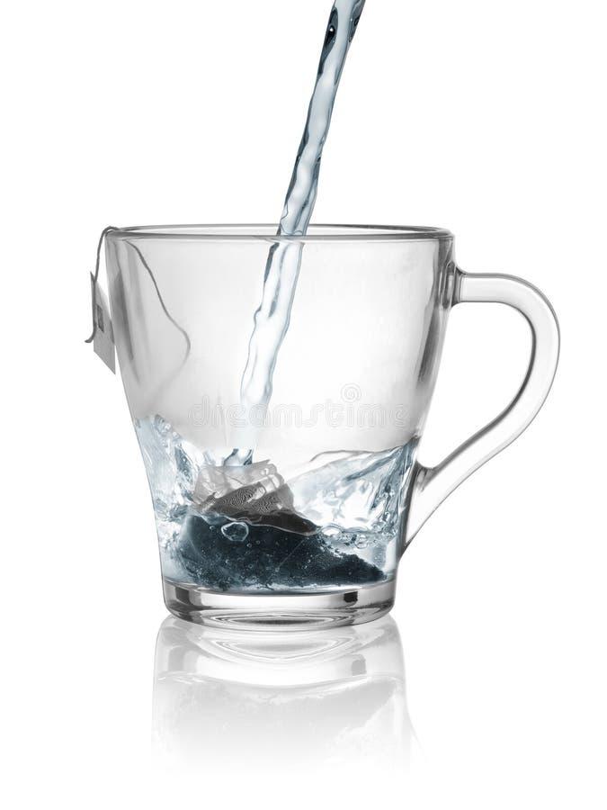 Кипяченая вода пропускает поток от чайника в стеклянной чашке с устранимой сумкой зеленого чая стоковое изображение