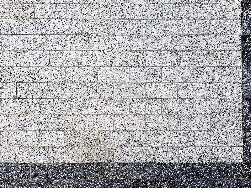 Кирпичная стена в белом и черном Текстура фасада плитки бела и черна Кирпичная стена в белом и черном стоковые фото