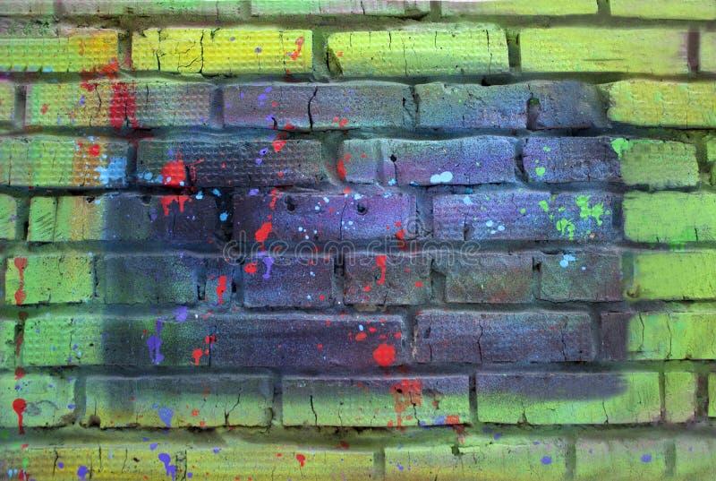 Кирпичная стена покрашенная с пестротканой краской стоковые фото