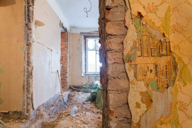 Кирпичная стена с старыми paperhangings часть интерьера квартиры во время на реновации стоковое изображение