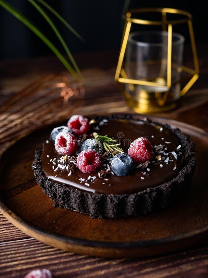 Кислый чизкейк шоколада со свежими ягодами вкусный десерт стоковое фото