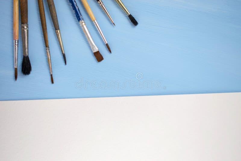 Кисти и лист бумаги на голубой предпосылке E r стоковое фото